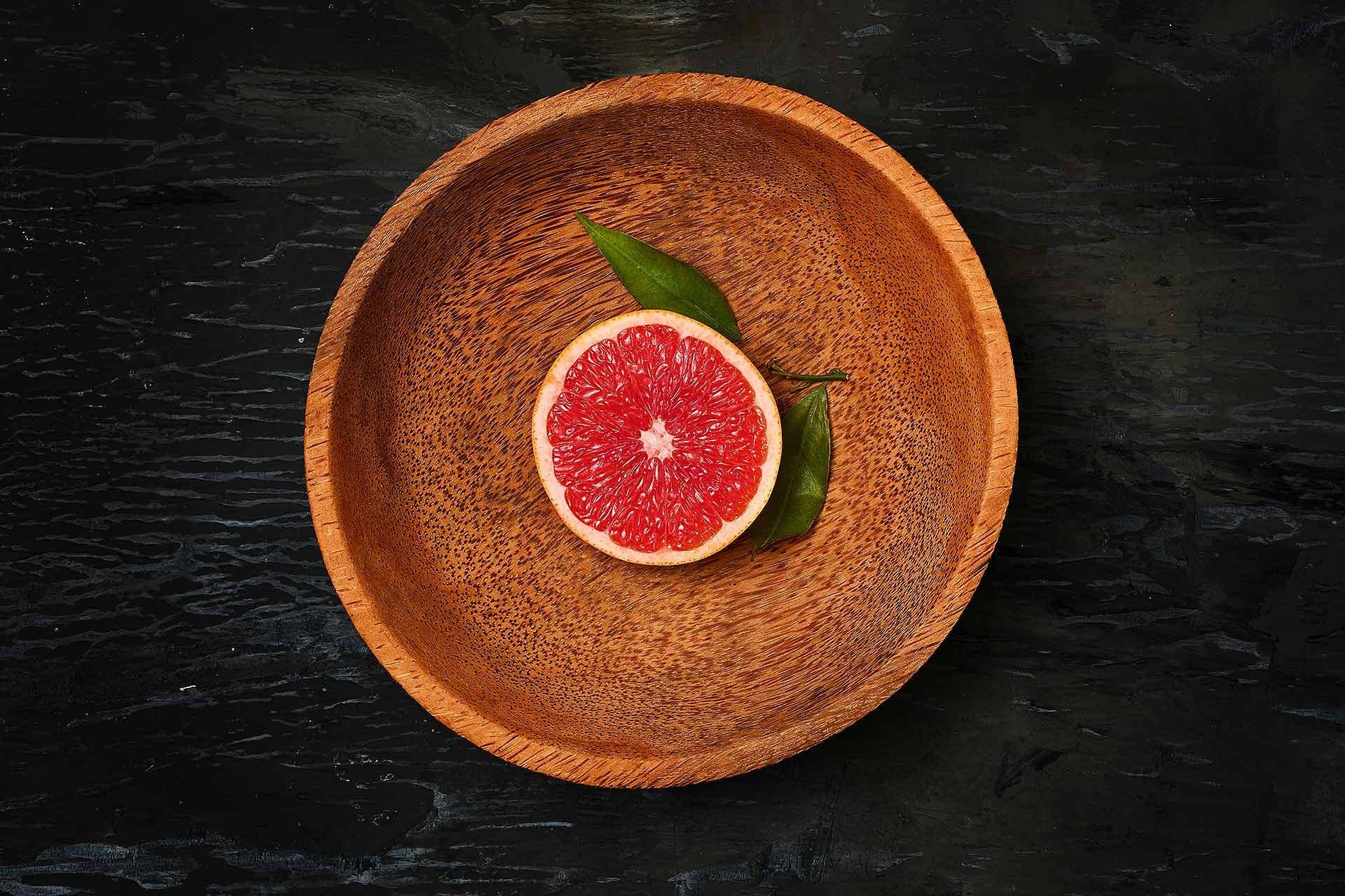 grapefruit-citrus-fruit-halves-on-wooden-plate-PHCQJD7